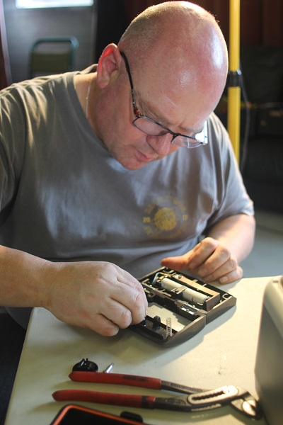 Volunteer at Penrith Repair Cafe fixing a sewing machine foot pedal
