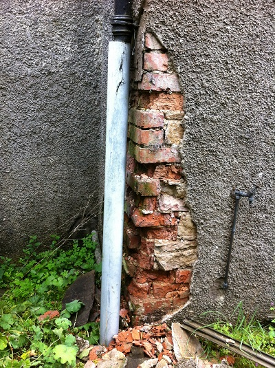 Brick decay due to leaky downpipe and cement render
