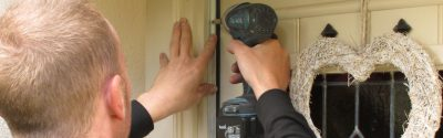 An installer fitting a door seal in Cumbria - CAfS draughtproofing scheme