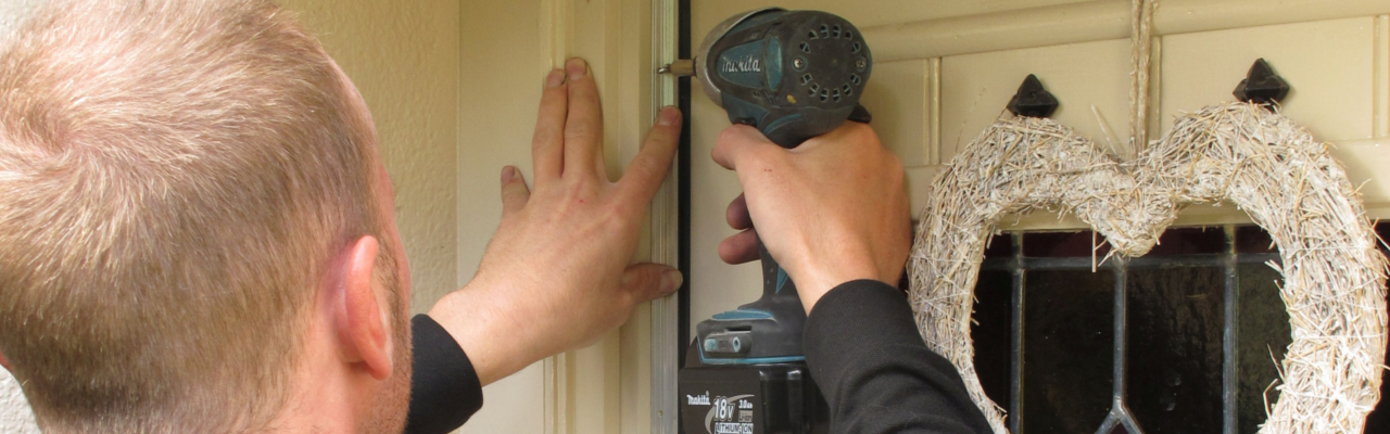 An installer fitting a door seal in Cumbria - CAfS draughtproofing scheme