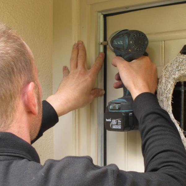 A professional installer fitting a draughtproofing door seal as part of the CAfS draughtproofing service