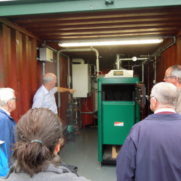 A group of people are shown a biomass boiler at the Cumbria Green Build Festival