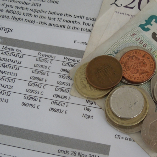 Home energy fuel bill with money on top of it - CAfS tariff switching service