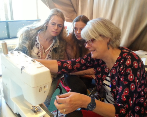A repair being carried out on a sewing machine while two women watch, at Alston Moor Repair Cafe