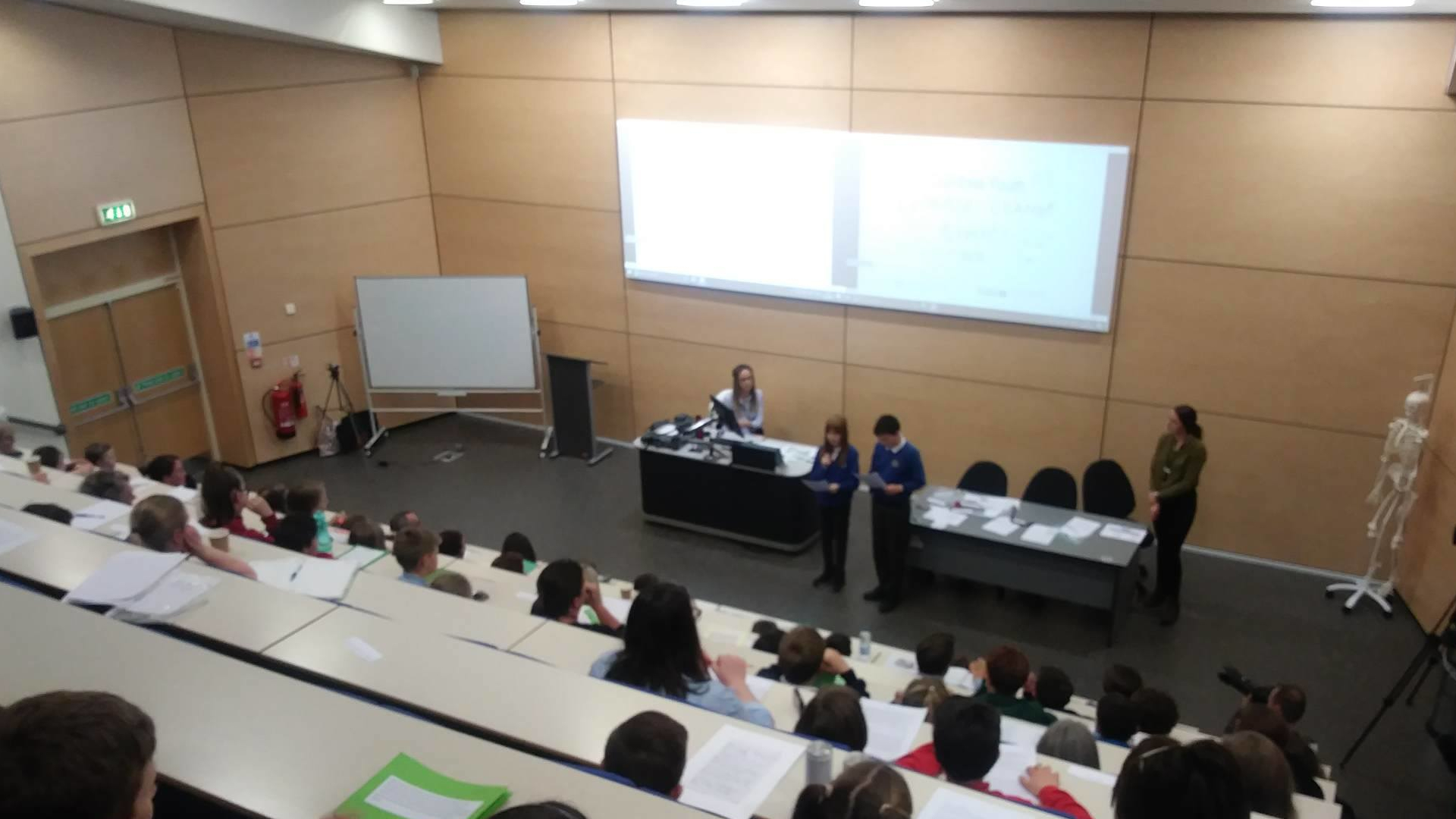 Young people in a lecture theatre listening as two students give a presentation on their fears about climate change, at Cumbria's first youth climate summit in Carlisle in April 2019