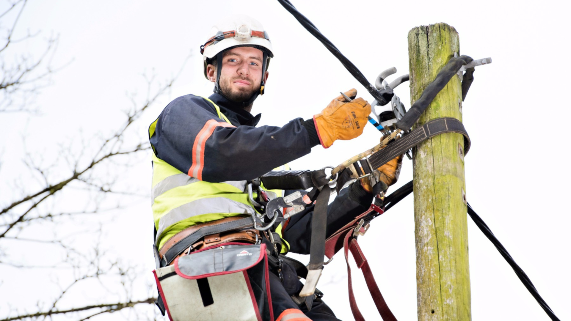 Electricity North West engineer working on cables at the top of an electricity pole