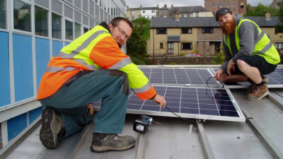 Keith Hodgson and Keir Marsden from Love Solar Ltd installing the solar PV panels on the roof of Alston schools