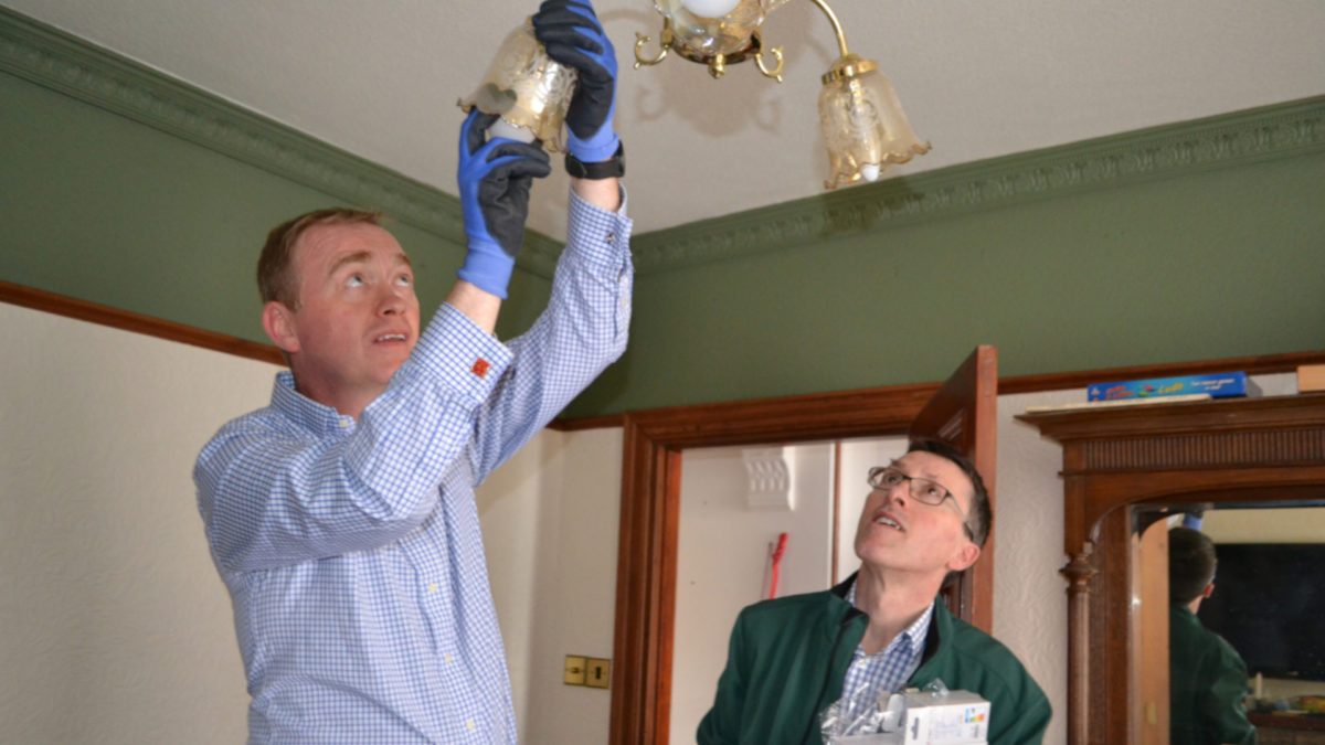 Tim Farron fits an LED light bulb on LEAP visit