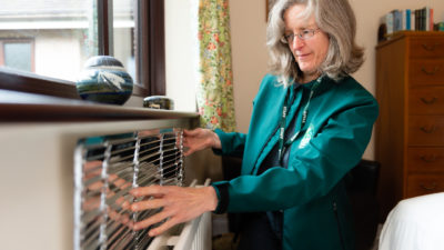 Tina from CAfS fits a radiator reflector during a Cold to Cosy Homes Cumbria visit