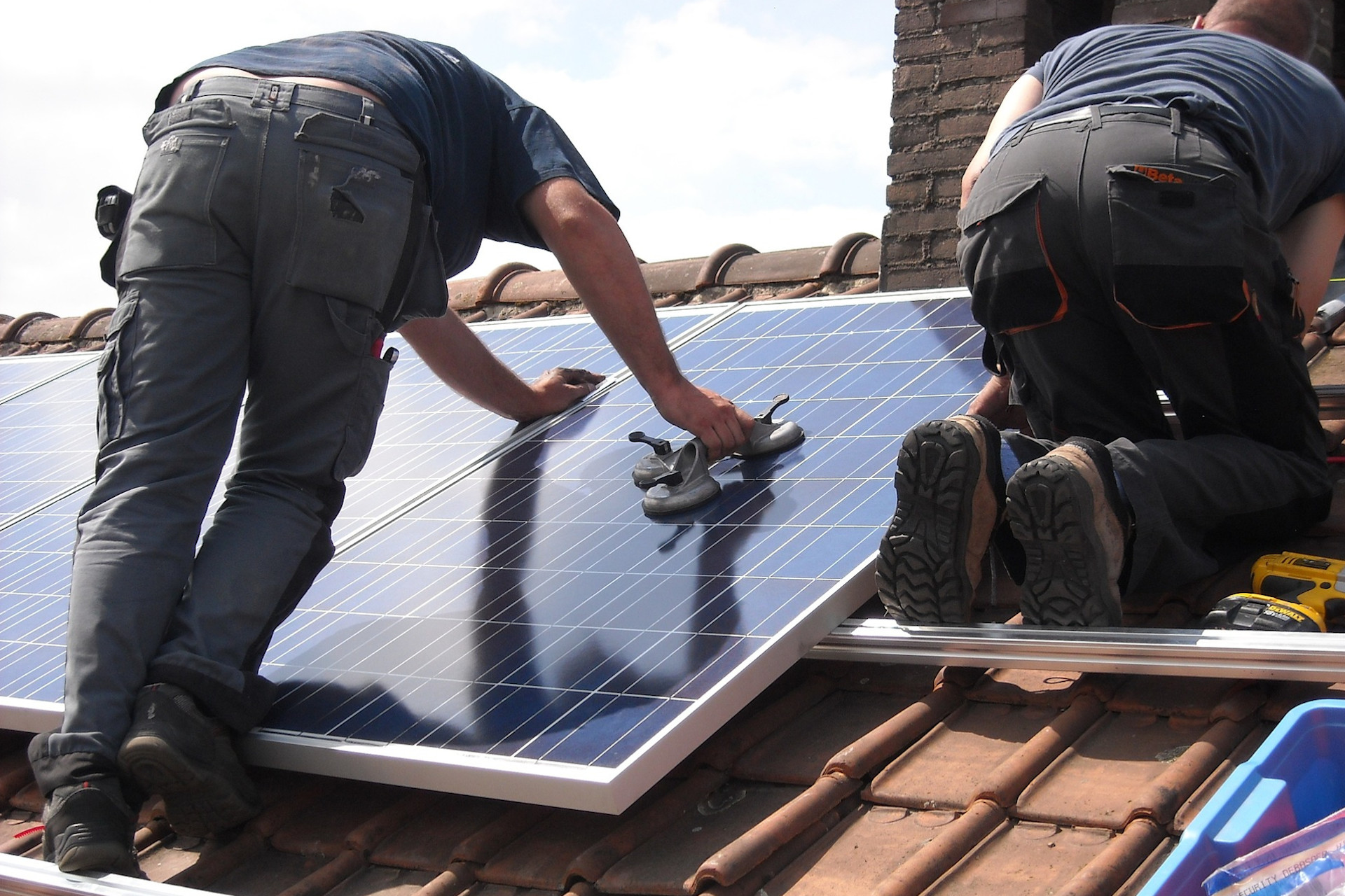 Two men fitting solar panels to a roof