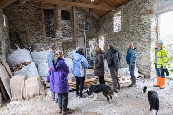A group standing in a stone barn