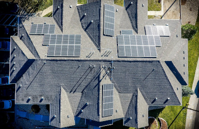 A large house from above with solar panels on the roof