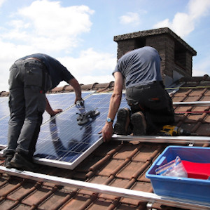 Two men installing solar panels on a roof