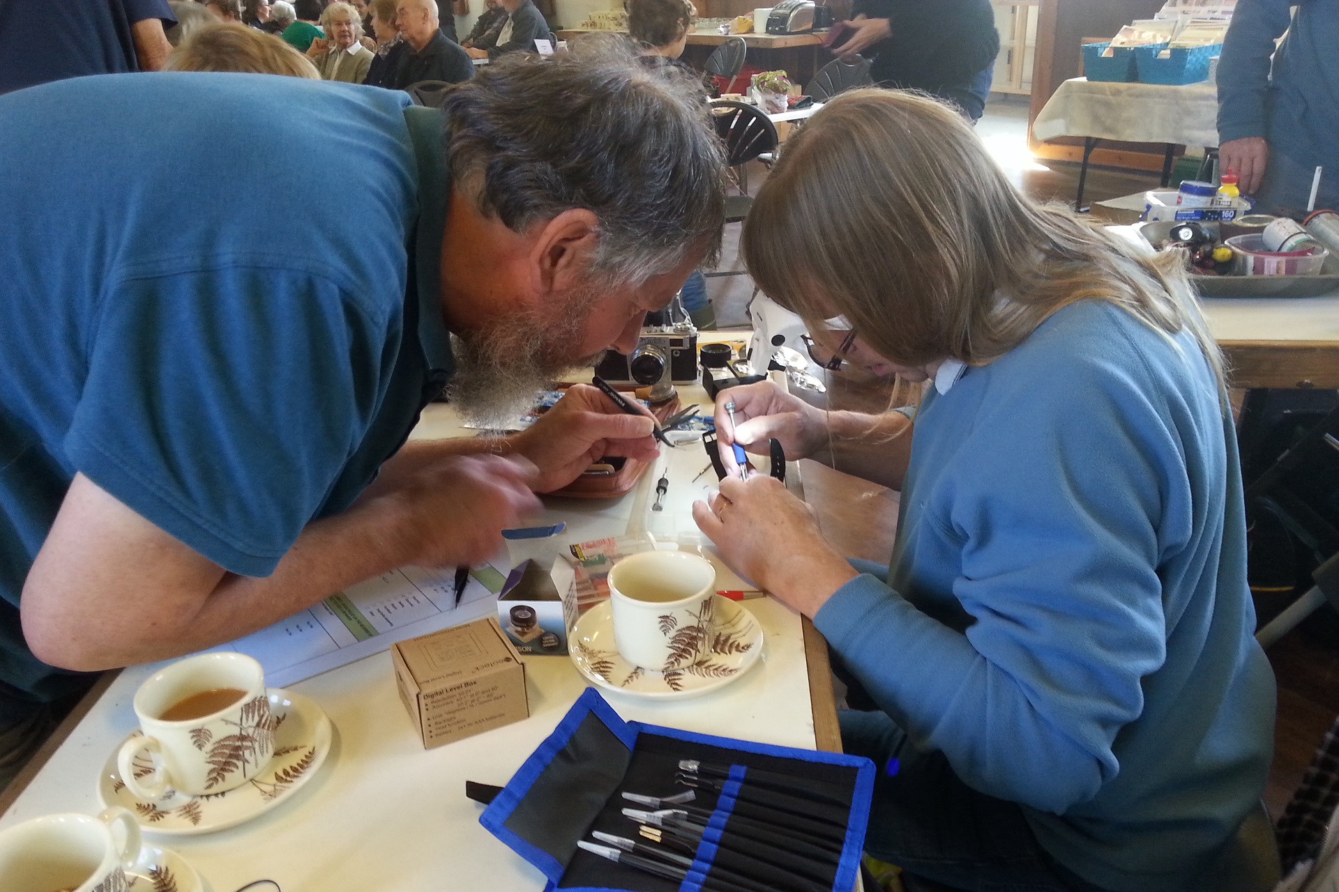 Two volunteers at Alston Moor Repair Cafe fixing an item