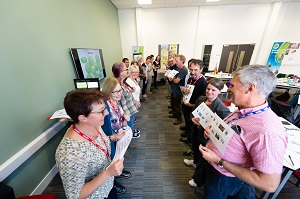 Two rows of attendees at a CAfS carbon literacy course in Carlisle, facing each other and holding up sheets