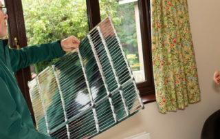 Andrew from CAfS installing a radiator reflector while the householder looks on