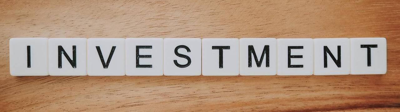 The word 'Investment' in Scrabble letters on a desk