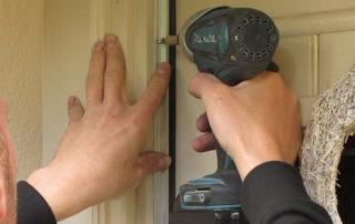 An installer using a drill to install a door draughtproofing seal
