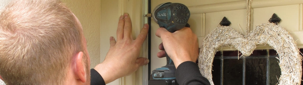 An installer using a drill to install a door draughtproofing seal