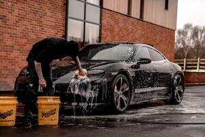 A man washing a car with buckets and a sponge